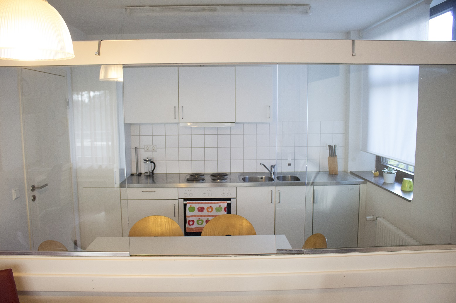 Image: kitchen unit in the background equipped with a fridge, 4 hotplates and a sink, in the foreground a kitchentable for 4 - 6 people