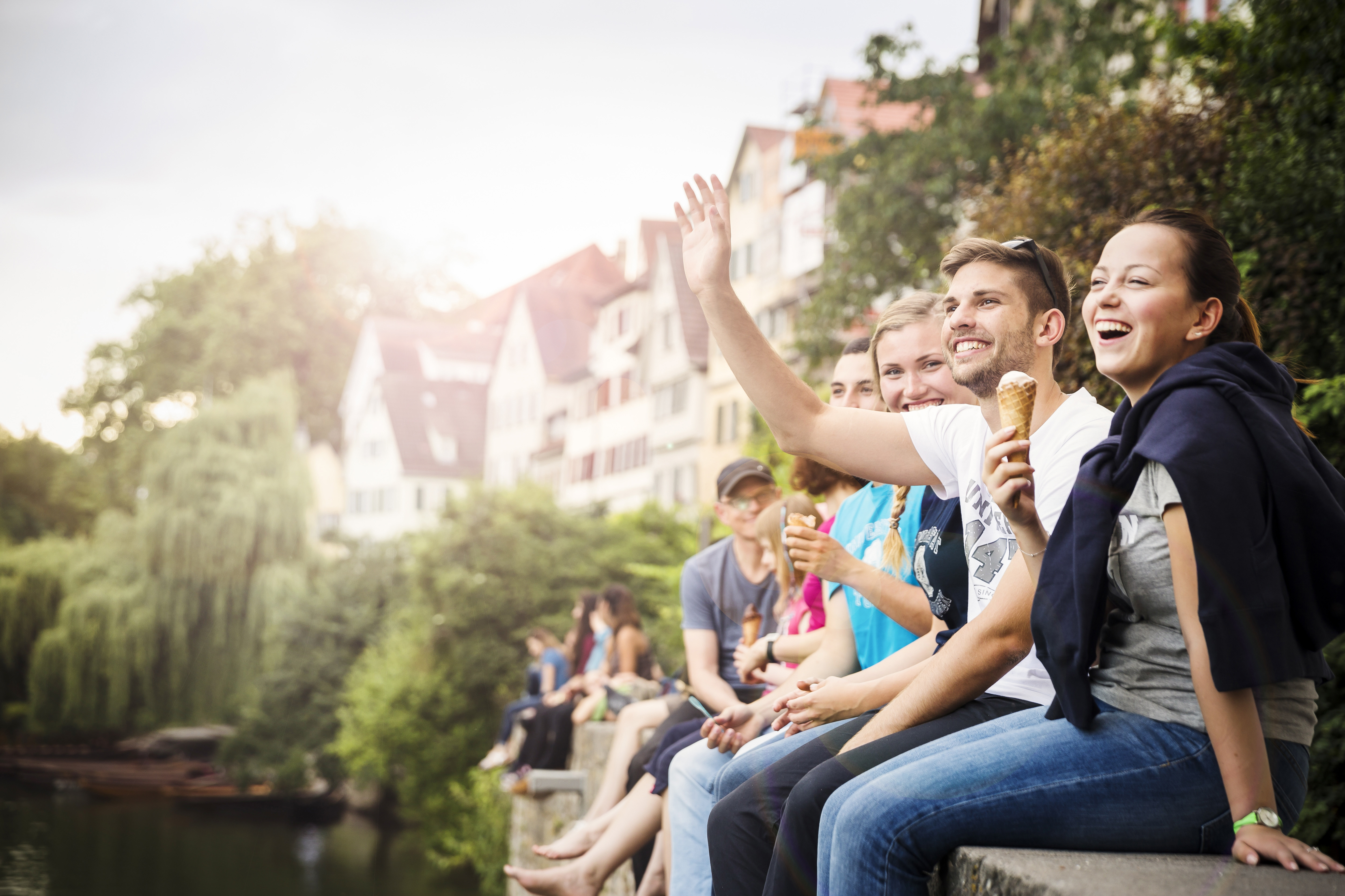 Students sitting on a wall next to the Neckar river
