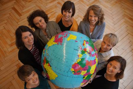 The Welcome Center staff members hold up an inflatable globe
